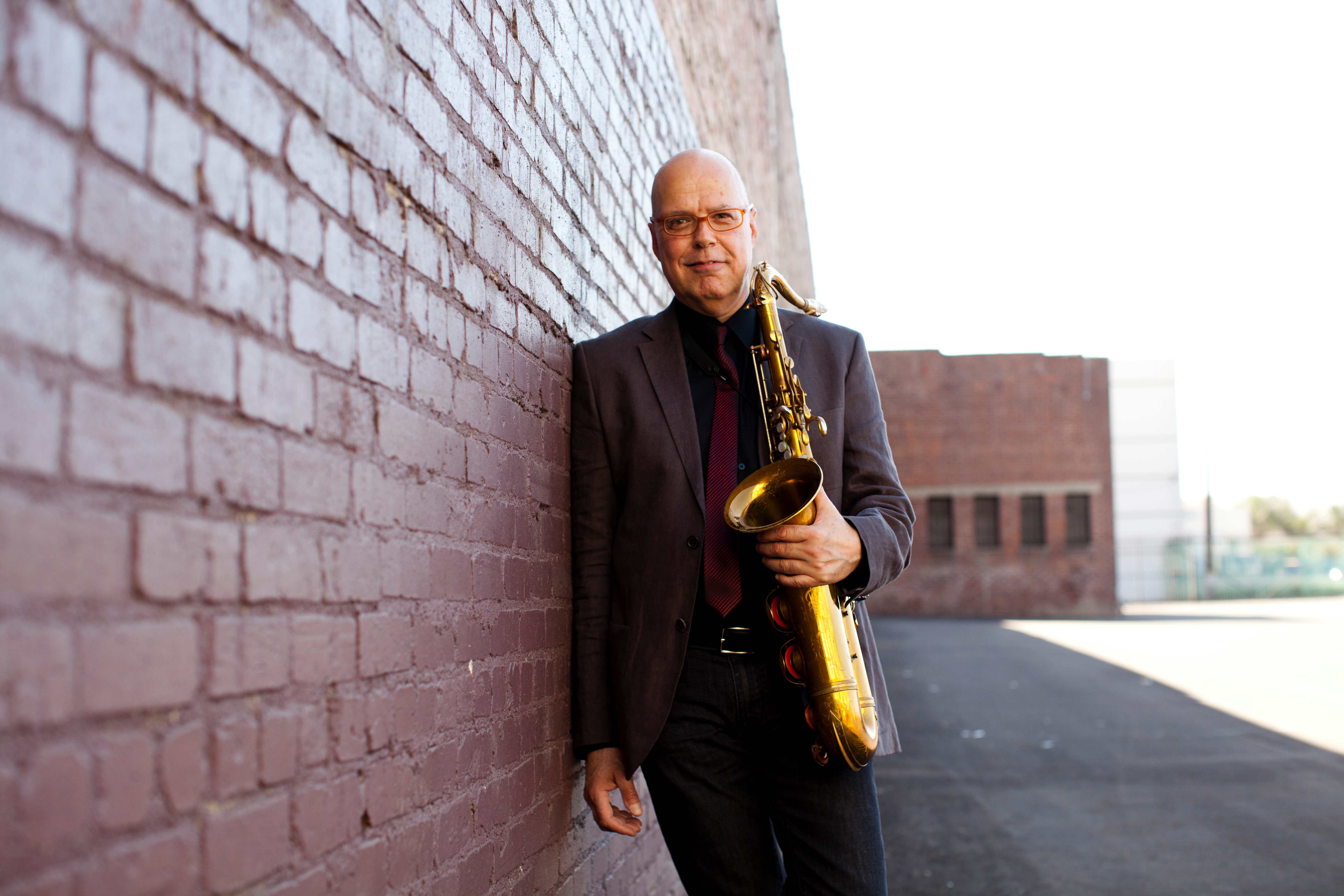 Bob Sheppard leaning against a brick wall holding a saxophone