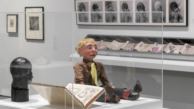 A ventriloquist dummy in a brown shirt, yellow tie, and cowboy boots sits next to an open book and a black leather bust in a vitrine